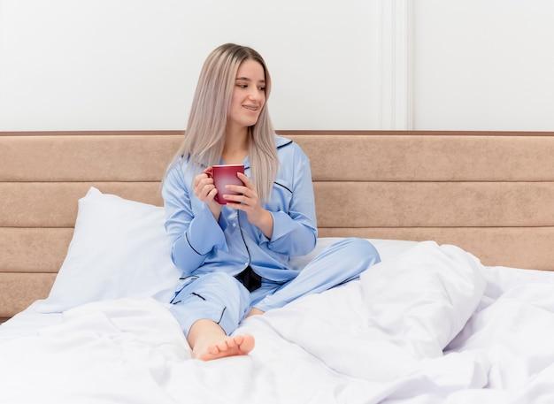 Jovem mulher bonita de pijama azul sentada na cama com uma xícara de café olhando para o lado sorrindo, descansando, aproveitando o tempo da manhã no interior do quarto