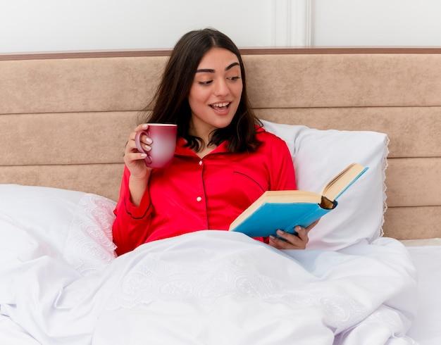 Jovem mulher bonita de pijama vermelho sentada na cama com uma xícara de café e um livro relaxante, aproveitando o fim de semana sorrindo com o rosto feliz lendo no interior do quarto sobre fundo claro