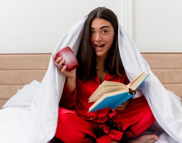Jovem mulher bonita de pijama vermelho sentada na cama, enrolando-se em um cobertor com uma xícara de café e um livro feliz e positivo sorrindo no interior do quarto na luz de fundo