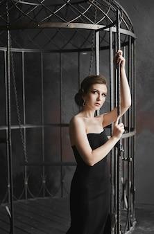 Jovem mulher bonita de vestido preto sai da enorme gaiola