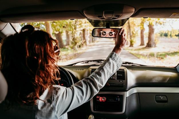 Jovem mulher bonita dirigindo um carro. conceito de viagens. vista de dentro. caminho da estrada de árvores