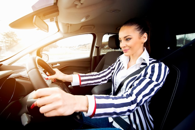 Jovem mulher bonita dirigindo um carro, sorrindo e concentrando-se no passeio.
