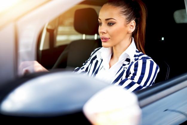 Jovem mulher bonita dirigindo um carro.