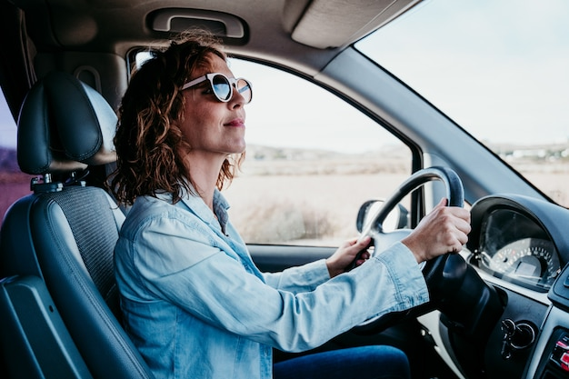 Jovem mulher bonita dirigindo uma van. conceito de viagens