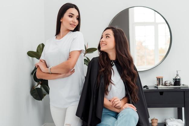Jovem mulher bonita discutindo penteado com seu cabeleireiro enquanto está sentado no salão de cabeleireiro