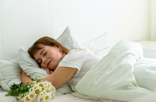 Jovem mulher bonita dormindo na cama com margaridas flores