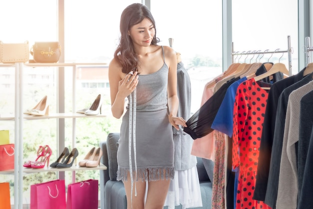 Jovem mulher bonita é alfaiate e designer.lady em compras e escolhendo roupas na loja