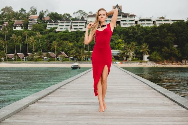 Jovem mulher bonita e atraente sozinha no cais em um hotel resort de luxo, férias de verão, vestido longo vermelho, cabelo loiro, roupa sexy, praia tropical, sedutora, sensual, sorridente