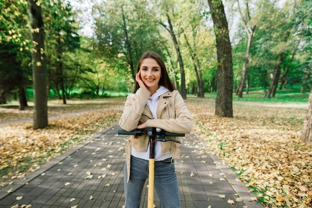 Jovem mulher bonita e elegante andando de scooter elétrica no parque de outono, transporte ecológico