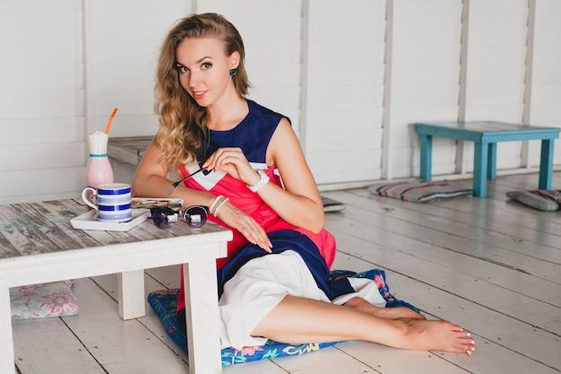 Jovem mulher bonita e elegante em sea café, comendo panquecas, batido de coquetel, óculos de sol, glamour, estilo resort, roupa da moda, sorrindo, vestido de cores marinhas
