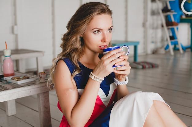 Jovem mulher bonita e elegante no café do mar, bebendo cappuccino quente, estilo resort, roupa da moda, sorrindo, vestido de cores marinhas, sentada no chão, férias, relaxe