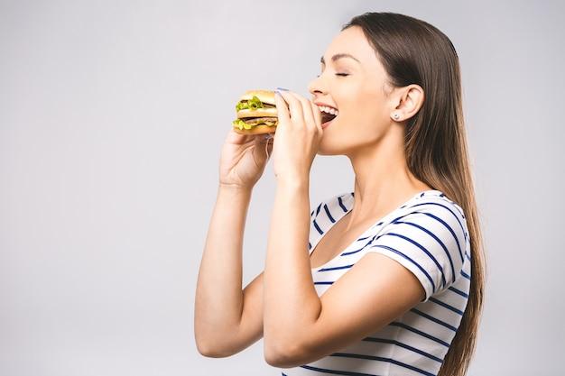 Jovem mulher bonita e feliz comendo hambúrguer