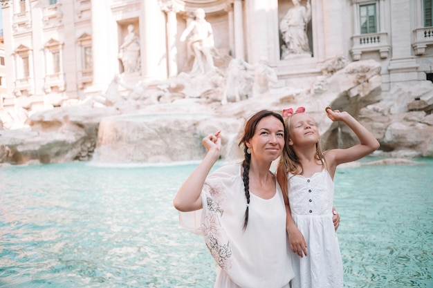 Jovem mulher bonita e menina perto da fonte fontana di trevi