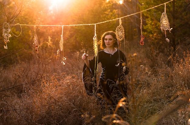 Jovem mulher bonita e misteriosa em vestido longo preto perto de coletores de sonho na floresta por do sol. silhueta feminina através dos raios de sol