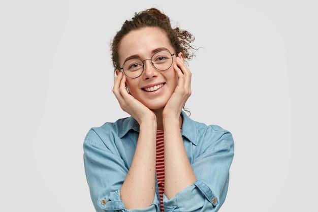 Jovem mulher bonita e otimista mantém as mãos nas bochechas, sorri positivamente, feliz com os elogios, usa óculos redondos e camisa jeans, isolada sobre a parede branca. conceito de emoções
