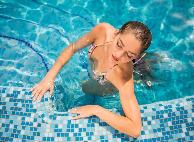 Jovem mulher bonita é relaxante na piscina.