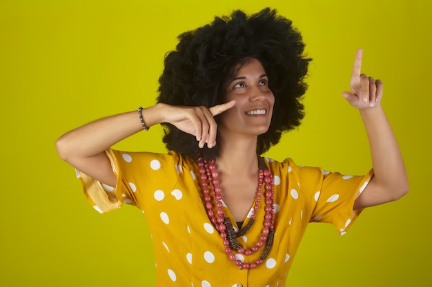 Jovem mulher bonita e sorridente com penteado afro encaracolado sobre fundo amarelo, apontando e olhando para cima, indicando a direção com os dedos.