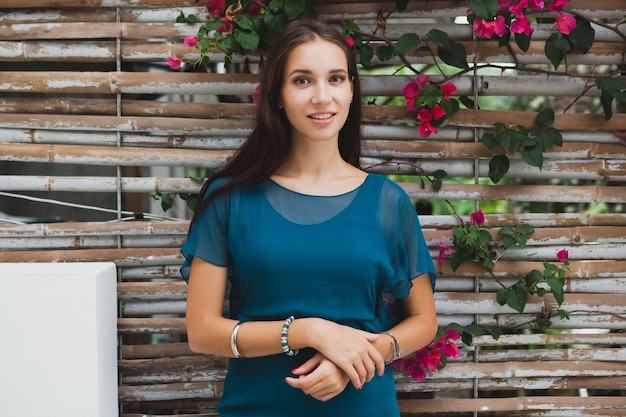 Jovem mulher bonita elegante em vestido azul, tendência da moda de verão, férias, jardim, terraço de hotel tropical, sorrindo