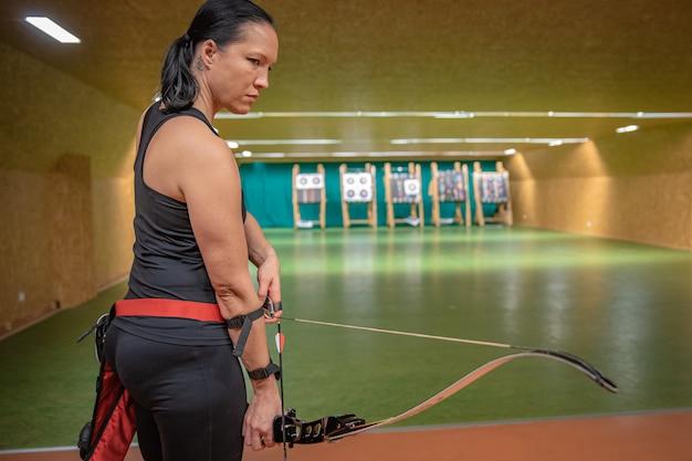 Jovem mulher bonita em competições esportivas, tiro com arco, visando o alvo