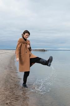 Jovem mulher bonita em elegantes roupas quentes, descansando e posando em uma praia de areia perto de um céu azul