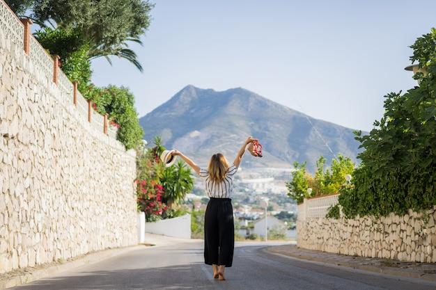 Jovem mulher bonita em férias pulando. em uma mão sandálias no chapéu de segunda mão.