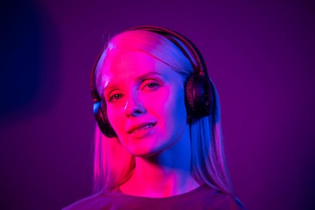 Jovem mulher bonita em fones de ouvido com iluminação colorida. dj em luz de néon. conceito de festa e música alta. a modelo olha para a câmera e sorri. fechar-se.