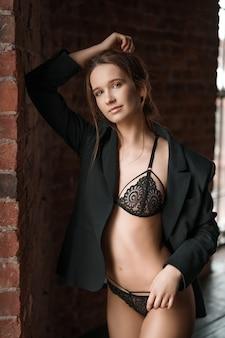 Jovem mulher bonita em lingerie pela janela