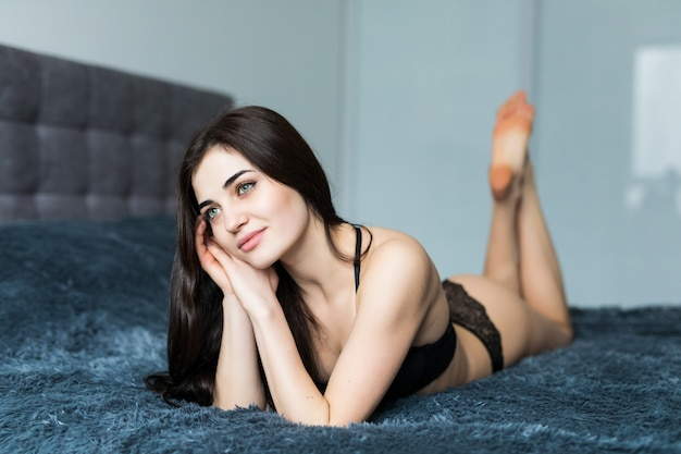 Jovem mulher bonita em lingerie preta sexy, sentada na cama