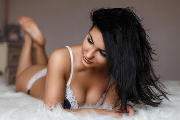 Jovem mulher bonita em lingerie sexy deitada na cama
