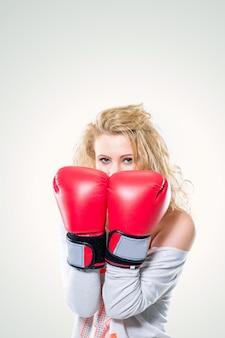 Jovem mulher bonita em luvas de boxe em branco