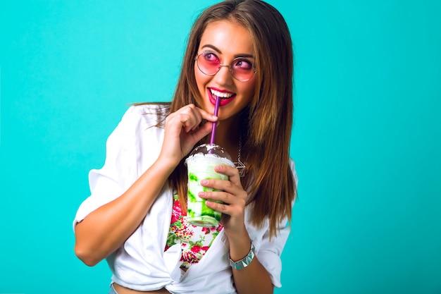 Jovem mulher bonita em miniburta jeans bebendo um smoothie saboroso, roupa vintage, óculos de sol com maquiagem