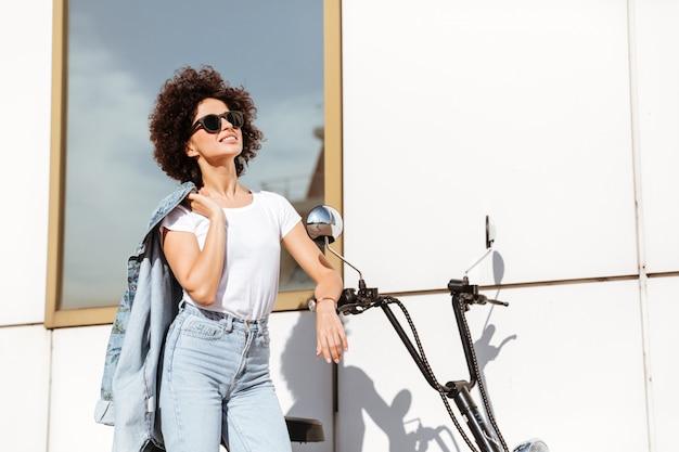 Jovem mulher bonita em óculos de sol posando Foto gratuita