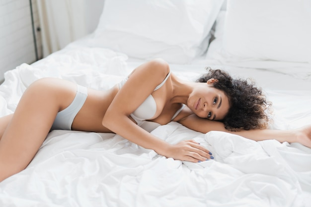 Jovem mulher bonita em roupa interior deitada na cama