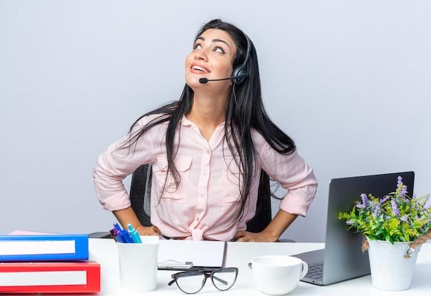 Jovem mulher bonita em roupas casuais com fones de ouvido e microfone olhando para cima feliz e positiva sorrindo, sentada à mesa com laptop sobre uma parede branca, trabalhando no escritório