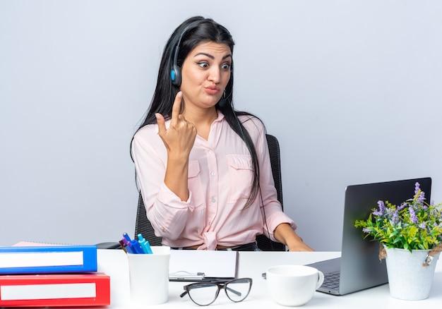 Jovem mulher bonita em roupas casuais com fones de ouvido e microfone, parecendo confusa e descontente, sentada à mesa com o laptop em branco