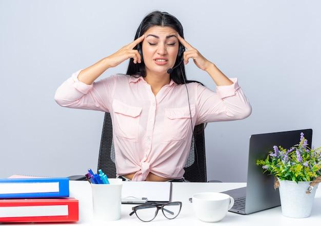 Jovem mulher bonita em roupas casuais com fones de ouvido e microfone parecendo irritada apontando com os dedos para as têmporas, sentada à mesa com laptop sobre uma parede branca, trabalhando no escritório