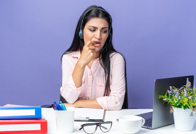 Jovem mulher bonita em roupas casuais com fones de ouvido e microfone, parecendo preocupada roendo as unhas, sentada à mesa com o laptop em azul