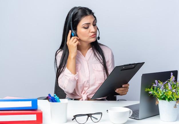 Jovem mulher bonita em roupas casuais com fones de ouvido e microfone segurando uma prancheta olhando para ela com uma cara séria sentada à mesa com o laptop em branco