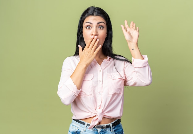 Jovem mulher bonita em roupas casuais surpresa e chocada cobrindo a boca com a mão em pé sobre a parede verde