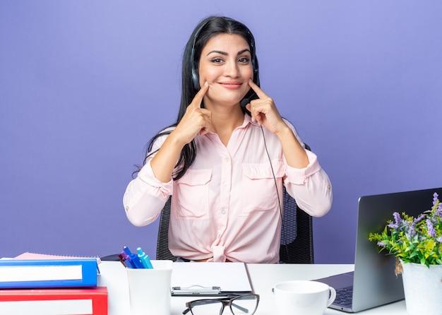 Jovem mulher bonita em roupas casuais usando fone de ouvido com microfone apontando para o sorriso dela, sentada à mesa com laptop sobre fundo azul, trabalhando no escritório