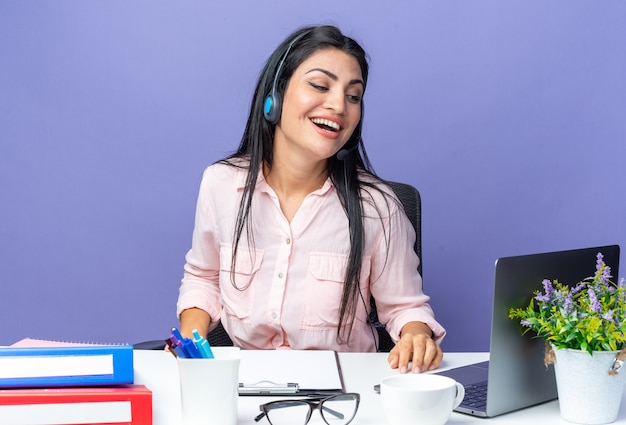 Jovem mulher bonita em roupas casuais usando fone de ouvido com microfone feliz e positiva sorrindo, sentado à mesa com o laptop em azul