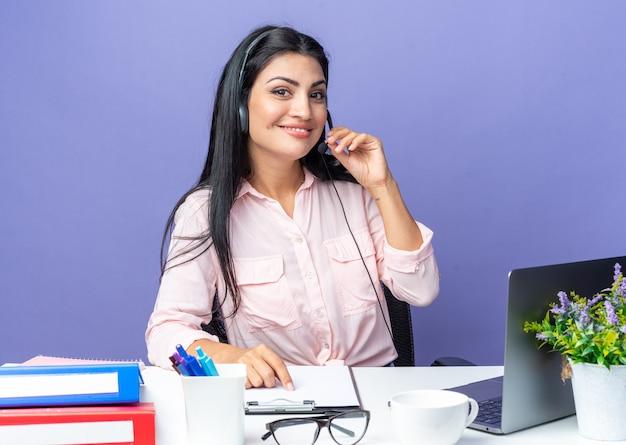 Jovem mulher bonita em roupas casuais, usando fone de ouvido com microfone, parecendo confiante, sorrindo, sentada à mesa com laptop sobre fundo azul, trabalhando no escritório