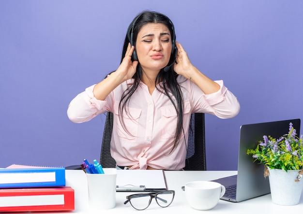 Jovem mulher bonita em roupas casuais, usando fone de ouvido com microfone, parecendo irritada, sofrendo com o barulho, sentada à mesa com o laptop sobre a parede azul, trabalhando no escritório