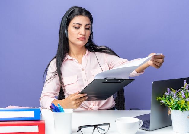 Jovem mulher bonita em roupas casuais, usando fone de ouvido com microfone, segurando a prancheta com páginas em branco, parecendo confiante sentada à mesa com o laptop sobre a parede azul, trabalhando no escritório