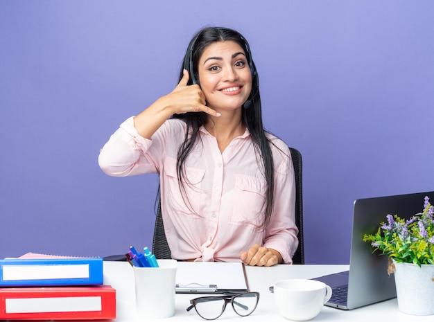 Jovem mulher bonita em roupas casuais usando fone de ouvido com microfone sorrindo, fazendo um gesto de me ligar, sentado à mesa com o laptop sobre a parede azul, trabalhando no escritório