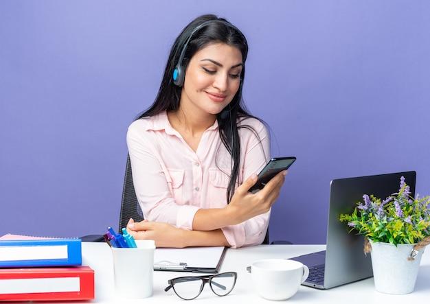 Jovem mulher bonita em roupas casuais usando fone de ouvido segurando um smartphone, olhando para ele, sorrindo, sentada à mesa com o laptop sobre a parede azul, trabalhando no escritório