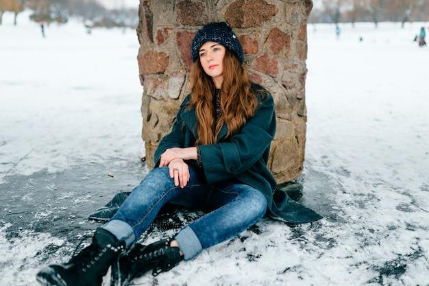 Jovem mulher bonita em roupas elegantes, com cabelos castanhos compridos, sentado sob a ponte no gelo no lago congelado em dia de inverno frio geada