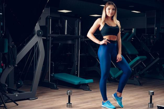 Jovem mulher bonita em roupas esportivas em uma academia, close-up