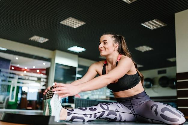 Jovem mulher bonita em roupas esportivas fazendo alongamento flexível enquanto está sentada no chão em um tapete na academia