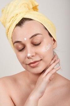 Jovem mulher bonita em topless aplicando creme nutritivo no rosto, olhos fechados, isolado na parede cinza